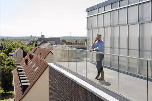Businessman talking over smart phone while standing in balcony against sky on sunny day - JOSEF01807