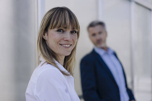 Smiling female professional with businessman standing against wall in greenhouse - JOSEF01825