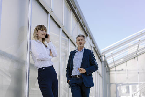 Businessman standing by female coworker talking over smart phone while standing by wall - JOSEF01834
