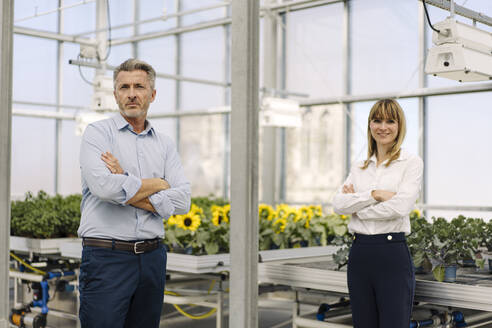 Confident male and female professionals with arms crossed standing in greenhouse - JOSEF01843