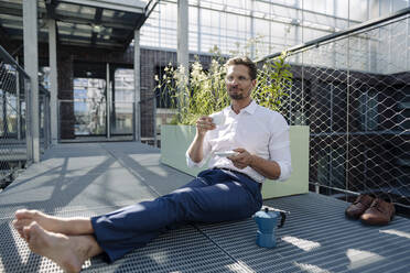 Male professional with coffee sitting on floor in plant nursery - JOSEF01882