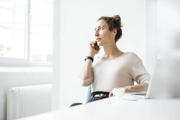 Businesswoman talking over smart phone while sitting with laptop on table - JOSEF01893