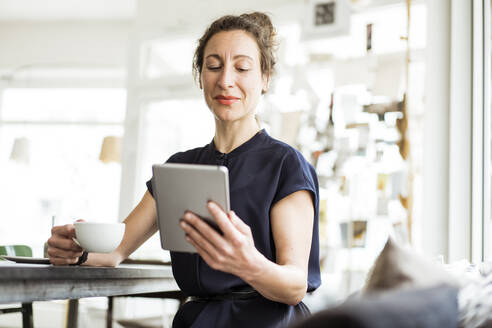 Businesswoman holding coffee cup using digital tablet while sitting at table - JOSEF01896