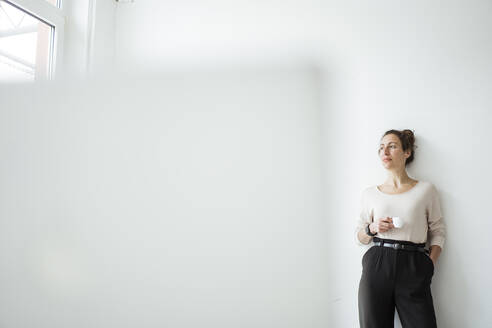 Businesswoman holding coffee cup contemplating while standing against white wall - JOSEF01911