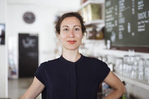Close-up of confident female entrepreneur standing in restaurant - JOSEF01929