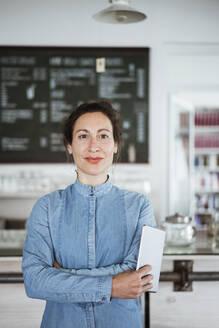 Female owner holding digital tablet while standing in restaurant - JOSEF01938