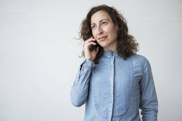 Businesswoman talking over mobile phone while standing against white wall - JOSEF01950