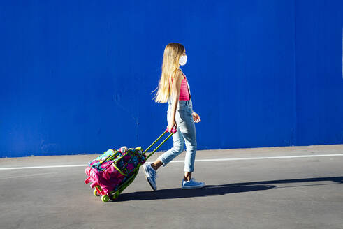 Blond girl walking with schoolbag on street against blue wall - JCMF01378