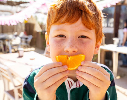 Little preteen redhead boy with freckles in casual clothes eating a slice of a orange and looking at camera - ADSF15410