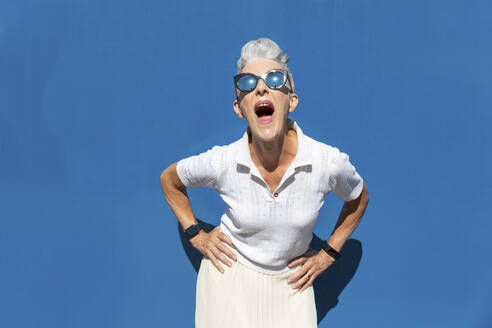 Woman with mouth open and hand on hip standing against blue wall during sunny day - WPEF03306