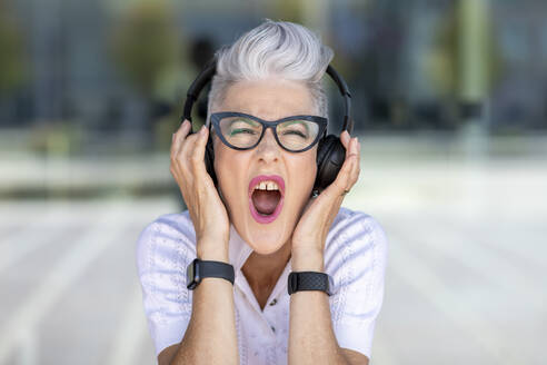 Excited senior woman screaming while listening to music through headphones - WPEF03324