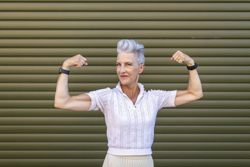 Senior woman flexing muscles while standing against shutter - WPEF03327