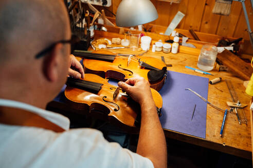 Back view of unrecognizable professional artisan luthier sitting at workplace and placing violin bridge on instrument - ADSF15629
