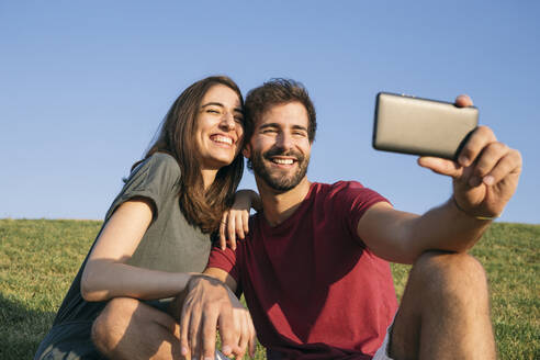Man taking selfie with woman while sitting on grass - ABZF03320