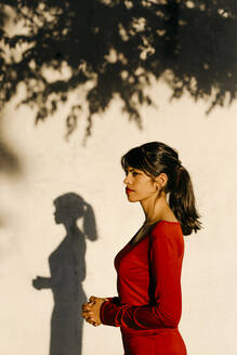 Woman with joined hands standing against wall during sunset - TCEF01048