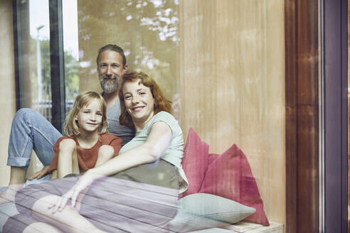 Smiling family relaxing on bed at home seen through window - MCF01357