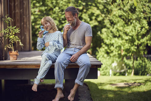 Father and daughter brushing teeth while sitting in yard - MCF01462