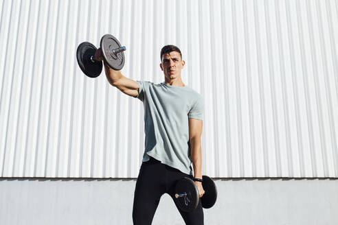 Athlete exercising with dumbbell while standing against wall - MIMFF00195