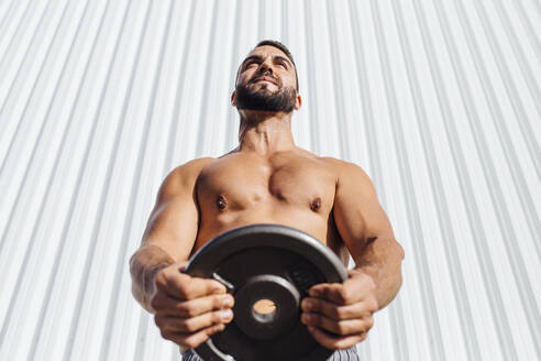 Man with muscular build holding weight while standing against wall - MIMFF00201