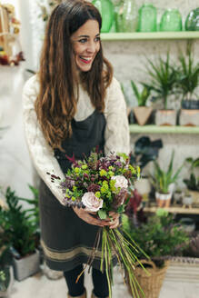 Smiling woman holding bunch of flowers while standing at flower shop - MRRF00400