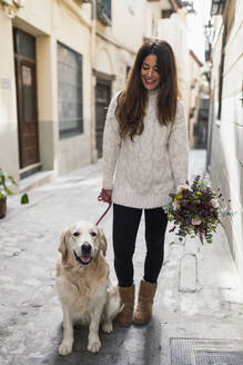 Woman holding bouquet while standing with dog on road in city - MRRF00409