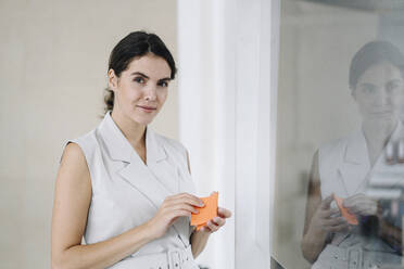 Woman holding sticky notes while standing by glass wall at office - KNSF08430
