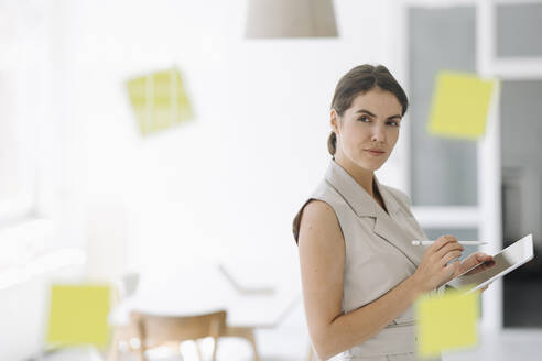 Businesswoman brainstorming while using digital tablet at office - KNSF08445