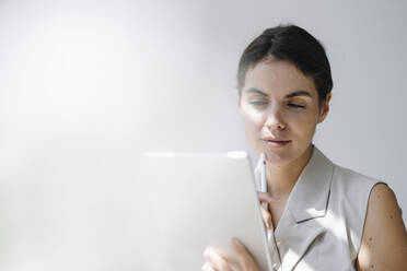 Thoughtful businesswoman using digital tablet at office - KNSF08448