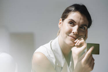Thoughtful woman smiling while holding business card at office - KNSF08454