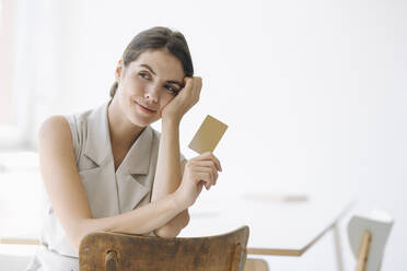 Smiling woman holding business card while sitting on chair at office - KNSF08457