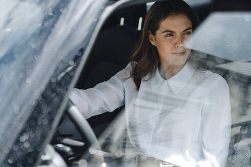 Businesswoman looking away while sitting in car - KNSF08517