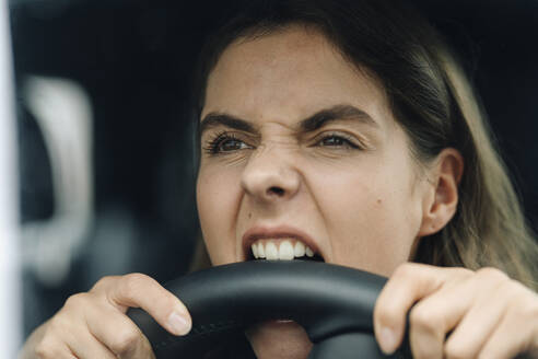 Close-up of angry woman biting steering wheel while while sitting in car - KNSF08523
