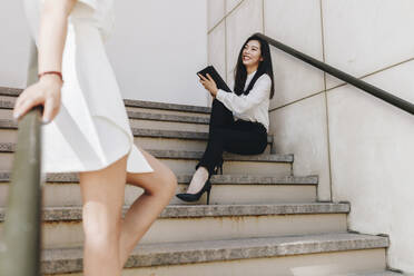 Businesswoman standing near smiling coworker on staircase - MRRF00415