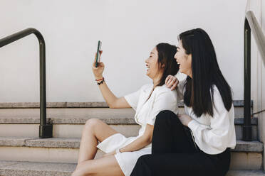 Coworkers taking selfie while sitting on staircase - MRRF00418