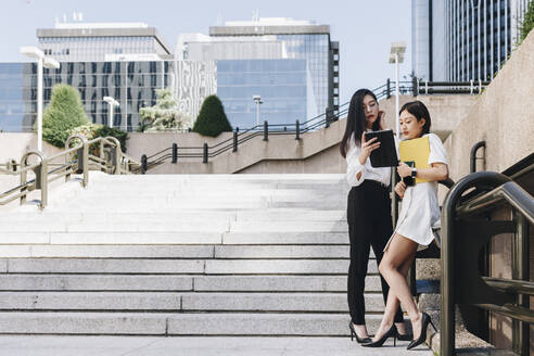 Female entrepreneurs standing on staircase against downtown district while using digital tablet - MRRF00427