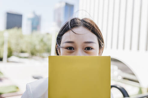 Female entrepreneur covering face with book while standing against financial district - MRRF00433
