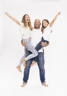 Father carrying cheerful daughters while standing against white background - SDAHF00962