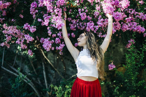 Beautiful woman with arms raised standing against flowers in park - DCRF00829