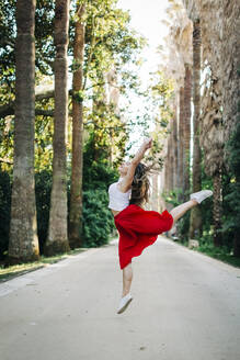 Young woman jumping while dancing on road amidst trees in park - DCRF00835