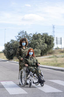 Female army soldier helping military officer sitting on wheelchair while wearing protective face mask - OCMF01664