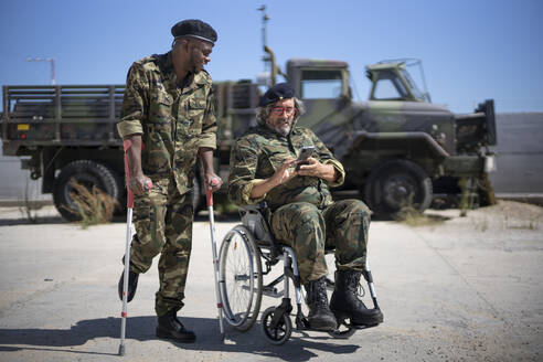 Injured army soldier holding crutches while standing with disabled colleague on wheelchair looking at smart phone during sunny day - OCMF01688
