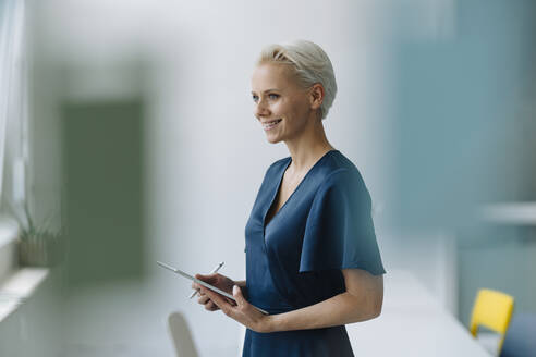 Smiling businesswoman with digital tablet looking away while standing in office - KNSF08578