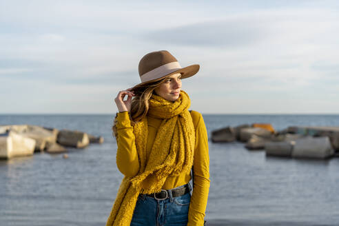 Thoughtful woman wearing sun hat while looking away against sea - AFVF07247