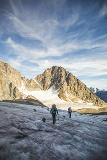 Two men cross a glacier through a high mountain pass. - CAVF88796