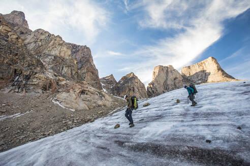Two mountain climbers traverse a glacier below Mount Asgard. - CAVF88799