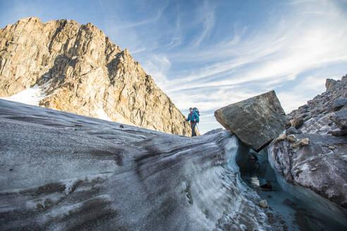 Backpacker crosses glacier in Akshayak Pass - CAVF88802