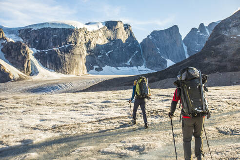 Rear view of two mountaineers exploring Auyuittuq National Park - CAVF88805
