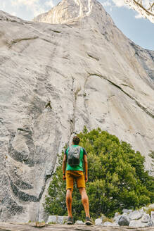 Young man looking up to El Capitan Mountain in Yosemite National Park. - CAVF88880