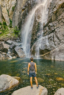 Young man standing on boulder, observing Yosemite Falls. - CAVF88883