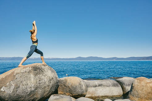 Young woman practicing yoga on Lake Tahoe in northern California. - CAVF88892